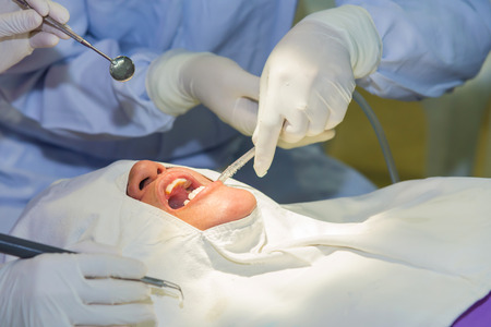 The doctor cleaning the teeth patient with ultrasonic tool.