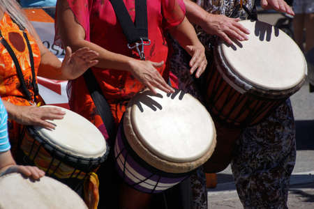 Drums played by women  in brightly colored clothes, Penticton, British Columbia, Canada