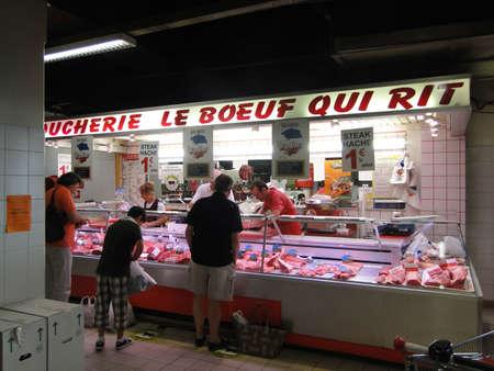 AVIGNON, FRANCE - OCT 2, 2011 - Shopper  inspects the butcher shop  l in Les Halles, on Oct 2, 2011, in Avignon, France.