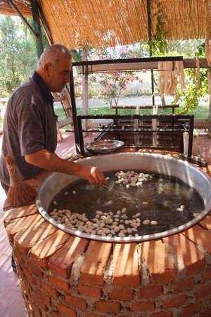 EPHESUS, TURKEY - MAY 25, 2014 - Boiling silkworm cocoons before unwinding silk,  Ephesus, Turkey