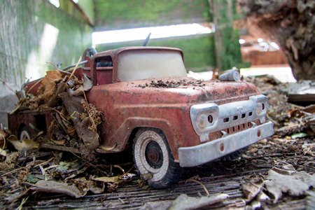 Photo for Old Antique 1960s Toy Fire Truck Covered in Leaves and Dirt - Royalty Free Image