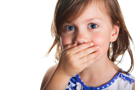 Portrait of a little girl who covered her mouth with hand, isolated on white background
