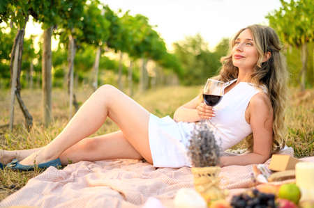 Photo pour Woman at the picnic with a glass of wine. Vine yard green backgrounds - image libre de droit