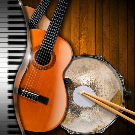Two acoustic guitars, piano keyboard and metallic old snare drum against a rustic wood background. Concept of music performance