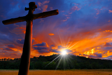 Cross silhouette at the beautiful sunset over the hill with cloudy sky