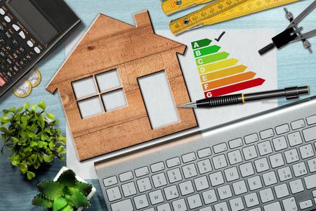 Foto de Energy efficiency rating graph on a desk with a wooden house model, calculator, folding ruler, drawing compass, pencil and a computer keyboard - Imagen libre de derechos