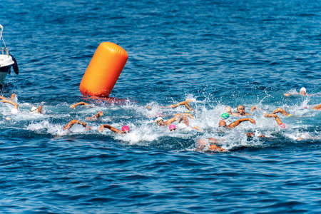 Swimming competition in the Mediterranean sea (Trofeo del Gro), in front of the ancient village of Tellaro. A group of freestyle swimmers is competing in the blue water
