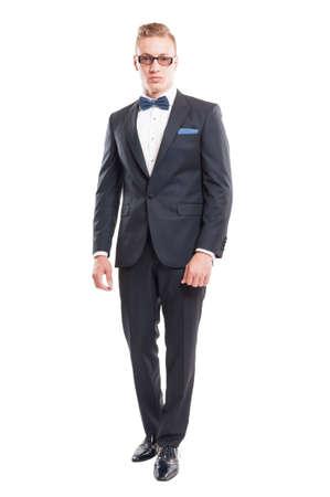 Elegant male model wearing suit, bowtie and sun glasses