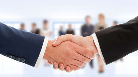 Photo pour Businessmen hand shake with business people in background. Congratulation or cooperation concept - image libre de droit