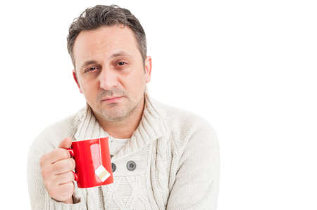 Sick man with sad face suffering of flu virus holding a cup of hot tea