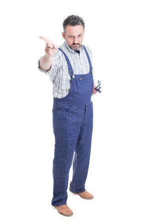 Handsome serious mechanic with wrench pointing finger in one direction or refusing to do a task isolated on white background
