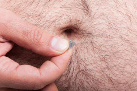 Man cleaning his hairy  belly of the lint or fuzz as umbilical hygiene concept