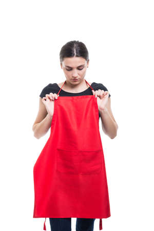 Female merchandiser or assistant adjusting her new apron received from work isolated on white background