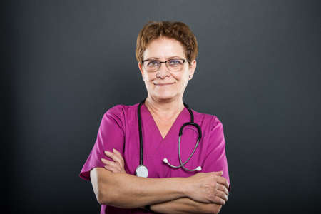 Portrait of senior lady doctor standing with arms crossed and smiling on black background