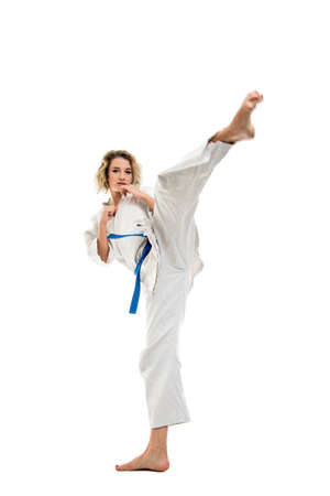 Photo pour Full body of woman making martial arts kicking up wearing white outfit  isolated on white background - image libre de droit