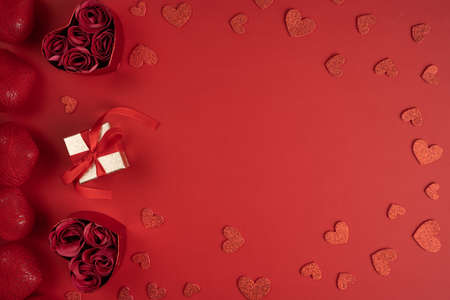 Photo pour Present for Valentine's day with heart shaped confetti. Gift box and heart shaped boxes with roses surrounded with red hearts, top view. - image libre de droit