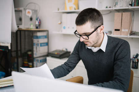 Photo pour Office worker reading paperwork in the office. Focused employee wearing glasses and reading documents in coworking space. - image libre de droit
