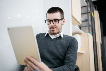 Photo pour Focused employee looking in to a tablet - image libre de droit