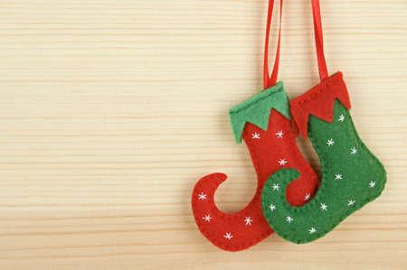 Handmade Christmas decorations - felt elf shoes over wooden background