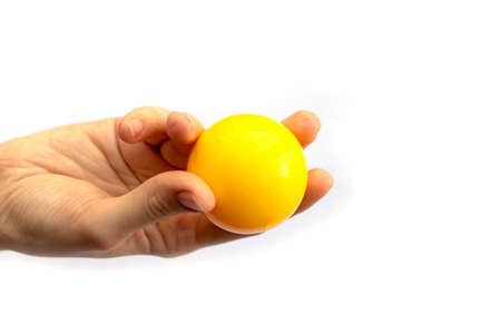 Foto de Female hand fingers holding yellow plastic ball isolated on white background - Imagen libre de derechos