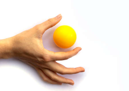 Foto de Fingers of a female hand touching a yellow plastic ball on a white background - Imagen libre de derechos