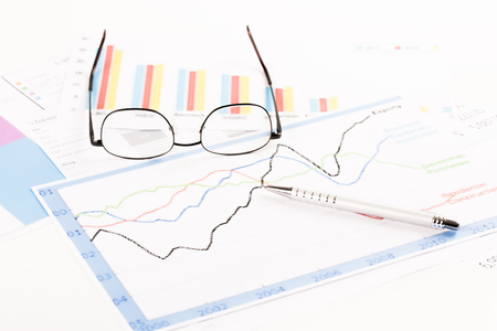 Financial analysis. Desk with graphs pen and glasses