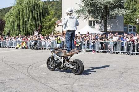 LE TRAIT, SEINE MARITIME, NORMANDY, FRANCE - SEPEMBER 01, 2018. Moto-show in central square of city. Tricks on ATV stuntmen, Stunt Riding - Wheelie, Stoppie and extreme acrobatics somersault on motorbike with a woman. Outdoor spectacle