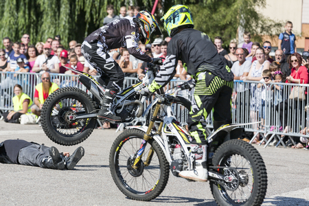 LE TRAIT, SEINE MARITIME, NORMANDY, FRANCE - SEPTEMBER 01, 2018. Moto-show in central square of city. Tricks on ATV stuntmen, Stunt Riding - Wheelie, Stoppie and extreme acrobatics somersault on motorbike with a man on the floor. Outdoor spectacle