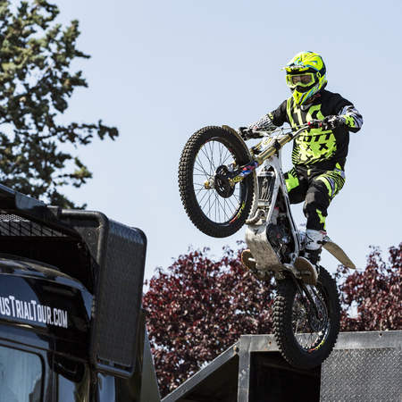 LE TRAIT, SEINE MARITIME, NORMANDY, FRANCE - SEPTEMBER 01, 2018. Moto-show in central square of city. Tricks on ATV stuntmen, Stunt Riding - Wheelie, Stoppie, jump in the air and extreme acrobatics somersault on motorbike with platform. Outdoor spectacle