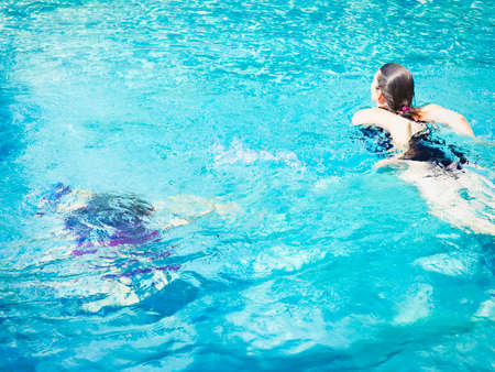 Photo pour Cheerful mature woman relaxing in swimming-pool in crystal water with summer light - image libre de droit