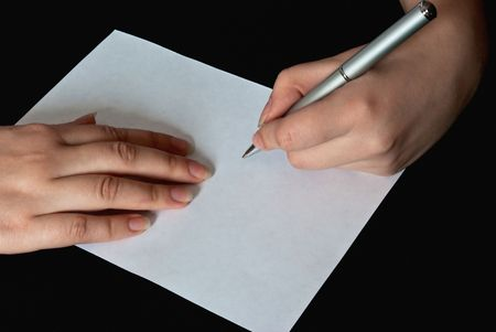 closeup view of left hand of a woman writing on a blank sheet of paper with a pen