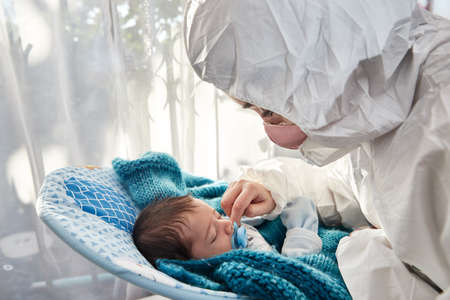 Foto de young mother with her newborn baby wearing a mask and surgical suit, accompanying and caring for her baby by the window in the midst of the covid19 pandemic - Imagen libre de derechos