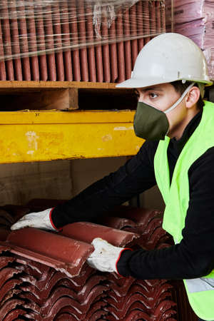 Foto de portrait of a young man wearing a mask and helmet in the middle of his work as a construction tool salesman, in the midst of covid 19 pandemic in the new normal - Imagen libre de derechos