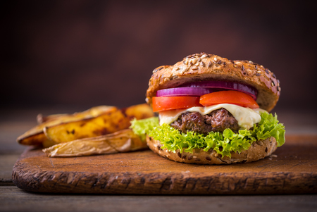 Photo pour Home made hamburger with green salad and with american potatoes behind. Brown wooden background. - image libre de droit