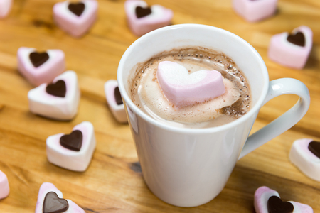 Marshmallow hearts and yummy hot chocolate drink on a wooden table. Love of sugary food or Valentines day concept