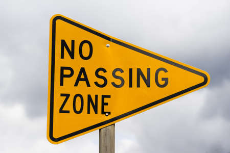 Photo for a reflective sign bolted to a post says no passing zone - Royalty Free Image
