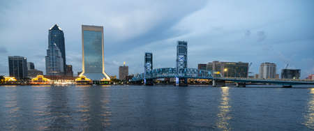 Building lights reflect in the St Johns River as night fall and a storm passes over Jacksonville Florida