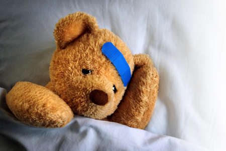 Photo of a sick teddy bear with a blue bandage in bed