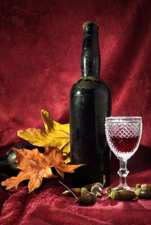 Vintage red wine glass and bottle with fall decoration details