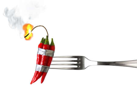 fork with group of red chilli peppers with burning fuse taped like dynamite