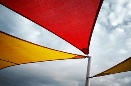 Three angular canvas awnings supported by a white pole against a cloudy sky