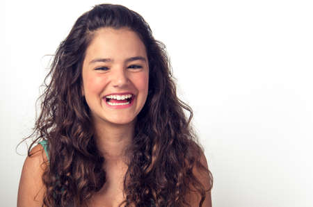 Portrait of a teenager brunette girl laughing over white background