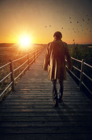 Foto de A man with long coat walking in a boardwalk into de sunset - Imagen libre de derechos