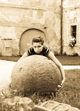 Young woman try to raise big stone ball