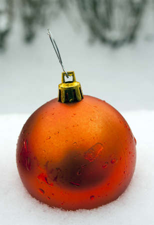 single orange christmas ornament in fresh snow with water droplets