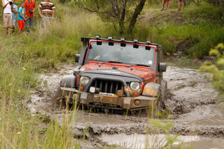 BAFOKENG - MARCH 8 Crush Orange Jeep Rubicon crossing muddy pond obstacle at Leroleng 4x4 track on March 8, 2014 in Bafokeng, Rustenburg, South Africa