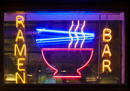 Photo for Ramen bar neon sign hanging outdoors and glowing in the evening, real horizontal picture - Royalty Free Image