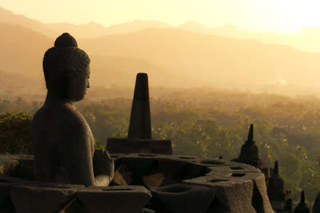 One of the many Buddha statues sitting inside a stupa on the top terraces of the ancient temple of Borobudur, Indonesia, facing a setting sun