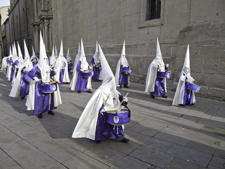 Nazarenes playing drums in a procession of Easter, Spanish religious belief