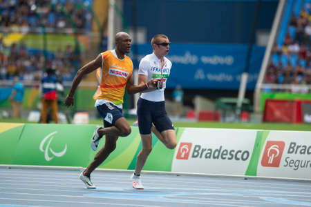 Rio, Brazil - september 10, 2016: ADOLPHE Timothee (FRA) Guide JOHN Jeffrey (FRA) during Men 100m - T11 Round 1 Heat 2, in the Rio 2016 Paralympics Games.